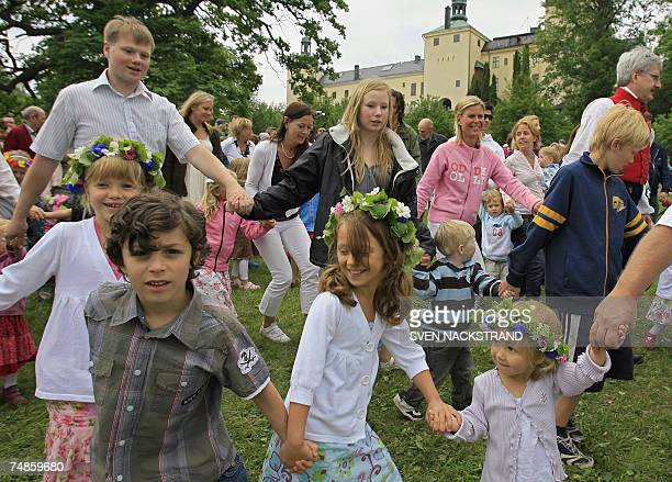 Swedes dance as they celebrate the Midsommar evening 22 June 2007 in the Tyreso Castle located 27 km southeast of Stockholm The real midsummer is 21...