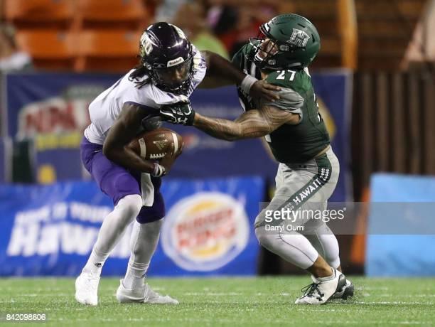 Tyrie Adams of the Western Carolina Catamounts is taken down by Solomon Matautia of the Hawaii Rainbow Warriors at Aloha Stadium on September 2 2017...