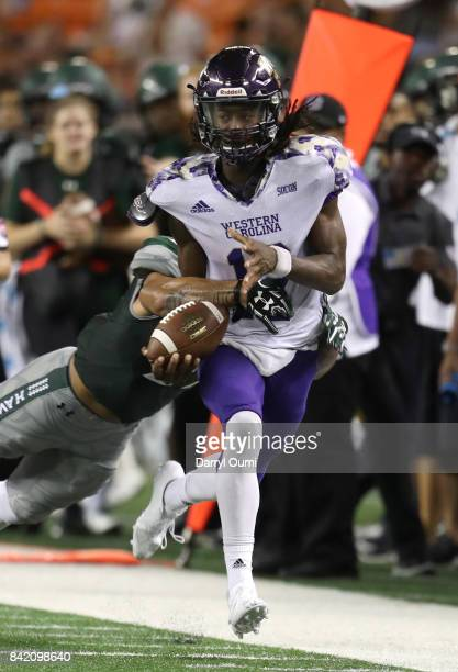 Tyrie Adams of the Western Carolina Catamounts is taken down by Solomon Matautia of the Hawaii Rainbow Warriors in the third quarter of their game at...