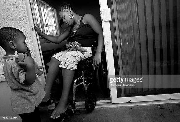 Tyrin Tisdale Jr then 2 watches as his mother struggles to get into their new home an apartment in South Los Angeles adapted to make wheelchair...