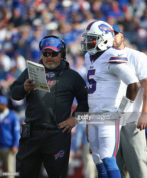 Tyrod Taylor of the Buffalo Bills listens to offensive coordinator Greg Roman on the sideline during NFL game action against the New England Patriots...