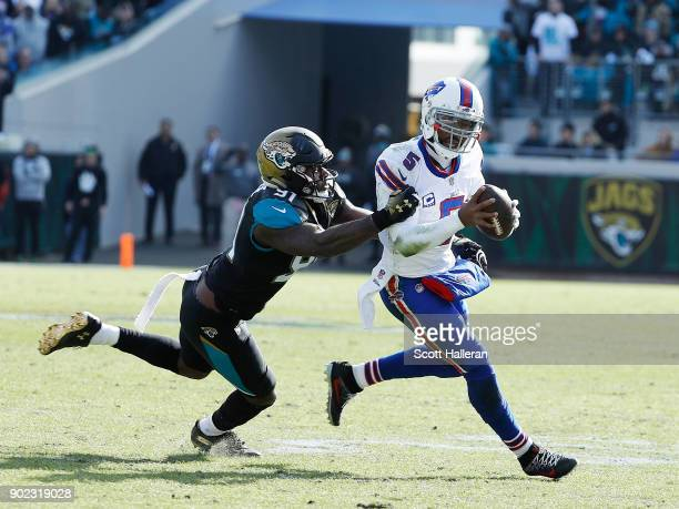 Tyrod Taylor of the Buffalo Bills runs away from Yannick Ngakoue of the Jacksonville Jaguars in the first half of the AFC Wild Card Round game at...