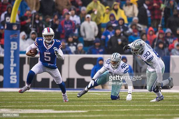 Tyrod Taylor of the Buffalo Bills runs on a quarterback scramble as Barry Church and Demarcus Lawrence of the Dallas Cowboys pursue on December 27...