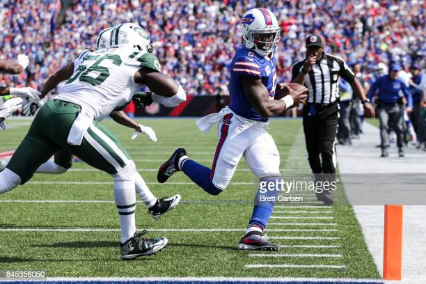 Tyrod Taylor of the Buffalo Bills runs the ball as Demario Davis of the New York Jets attempts to tackle him during the second half on September 10...