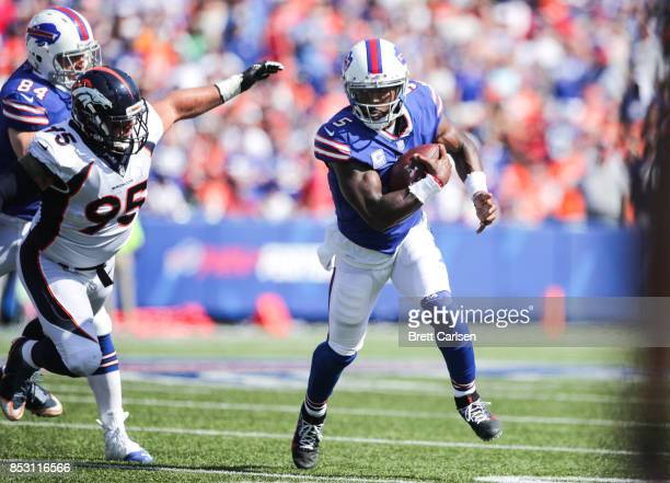 Tyrod Taylor of the Buffalo Bills runs the ball as Derek Wolfe of the Denver Broncos attempts to catch him during an NFL game on September 24 2017 at...