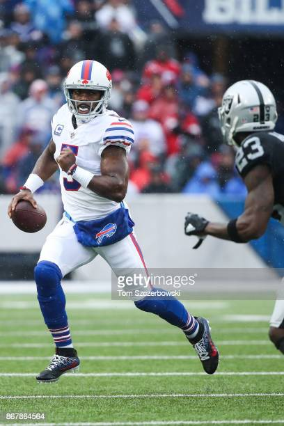 Tyrod Taylor of the Buffalo Bills runs the ball as Dexter McDonald of the Oakland Raiders attempts to catch him during the first quarter of an NFL...