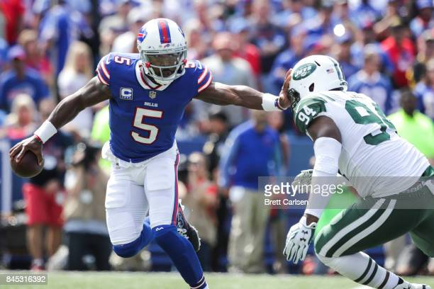 Tyrod Taylor of the Buffalo Bills runs the ball as Kony Ealy of the New York Jets attempts to tackle him during the first quarter on September 10...