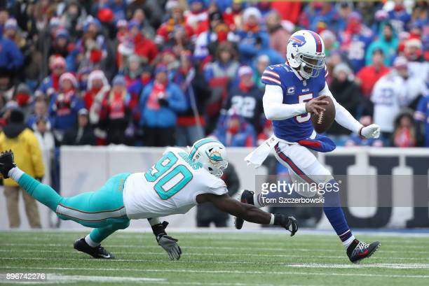Tyrod Taylor of the Buffalo Bills runs with the ball as he evades a tackle by Charles Harris of the Miami Dolphins during NFL game action at New Era...