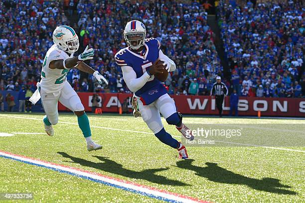 Tyrod Taylor of the Buffalo Bills runs with the ball as Jamar Taylor of the Miami Dolphins chases during the second quarter at Ralph Wilson Stadium...