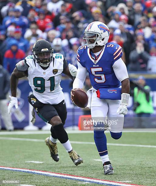 Tyrod Taylor of the Buffalo Bills scrambles as Yannick Ngakoue of the Jacksonville Jaguars chases him during NFL game action at New Era Field on...