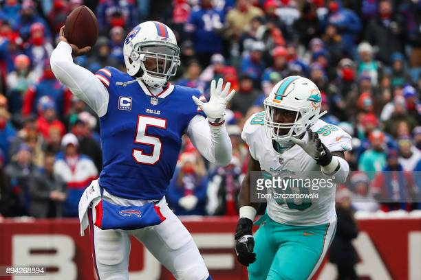 Tyrod Taylor of the Buffalo Bills throws the ball as Charles Harris of the Miami Dolphins attempts to defend him during the first quarter on December...
