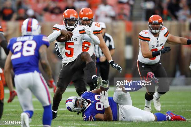 Tyrod Taylor of the Cleveland Browns breaks a tackle while pursued by Star Lotulelei of the Buffalo Bills in the first quarter of a preseason game at...