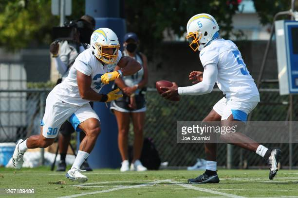 Tyrod Taylor of the Los Angeles Chargers hands the ball off to running back Austin Ekeler during Los Angeles Chargers Training Camp on August 19,...