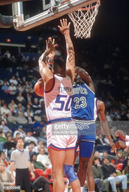 Tyrone Corbin of the Minnesota Timberwolves has his shot blocked by Melvin Turpin of the Washington Bullets during an NBA basketball game circa 1989...
