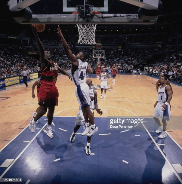 Tyrone Corbin, Small Forward for the Atlanta Hawks attempts to make a one handed lay up to the basket as Calbert Cheaney, Shooting Guard for the...
