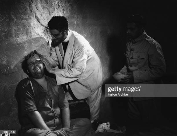 Tyrone Guthrie attends to Charles Laughton in a scene from the film 'Vessel Of Wrath' adapted from the story by W Somerset Maugham Also known as 'The...