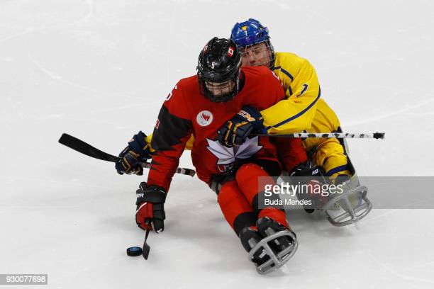 Tyrone Henry of Canada battles for the puck with Goran Karlsson of Sweden in the Ice Hockey Preliminary Round Group A game between Canada and Sweden...