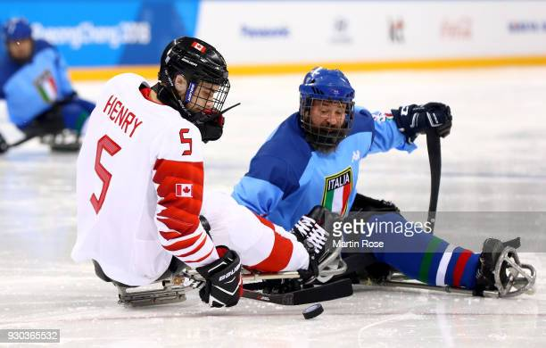 Tyrone Henry of Canada battles for the puck with Valerio Corvino of Italy in the Ice Hockey Preliminary Round Group A game between Canada and Italy...