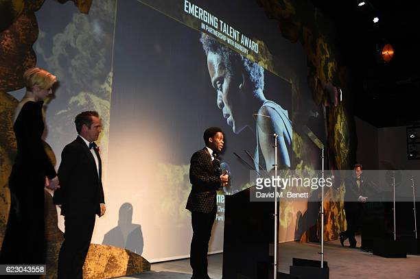 Tyrone Huntley winner of the Emerging Talent Award in partnership with Burberry accepts his award as presenter Tom Hollander and Elizabeth Debicki...