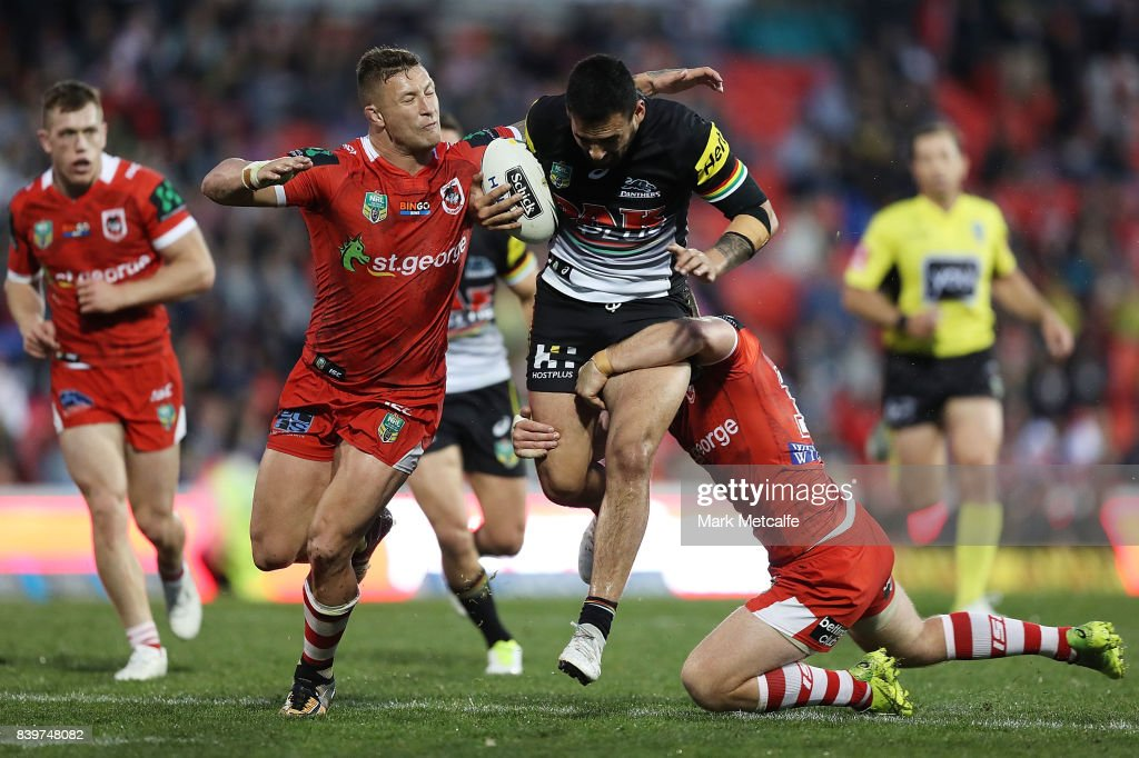 Tyrone May of the Panthers is tackled by Josh McCrone and Tariq Sims of the Dragons during the round 25 NRL match between the Penrith Panthers and the St George Illawarra Dragons at Pepper Stadium on August 27, 2017 in Sydney, Australia.