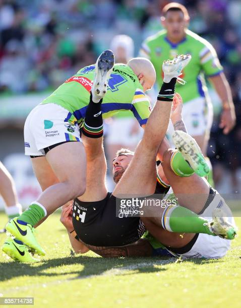 Tyrone May of the Panthers is tackled during the round 24 NRL match between the Canberra Raiders and the Penrith Panthers at GIO Stadium on August 20...