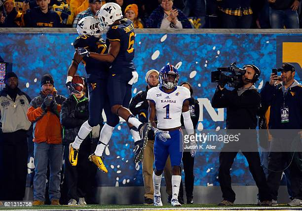 Tyrone Miller Jr #1 of the Kansas Jayhawks reacts after Justin Crawford of the West Virginia Mountaineers celebrates his 27 yard rushing touchdown in...