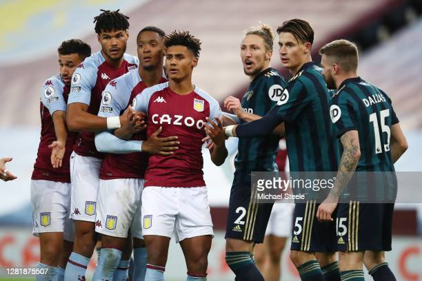 Tyrone Mings Ezri Konsa Ollie Watkins of Aston Villa and Luke Ayling Robin Koch and Stuart Dallas of Leeds United arrange themselves in a line for a...