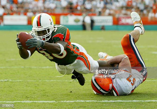 Tyrone Moss of the Miami Hurricanes breaks a tackle by Rich Scanlon of the Syracuse Orangemen and dives into the endzone for on the game winning nine...