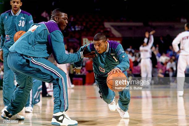 Tyrone 'Muggsy' Bogues of the Charlotte Hornets dribbles against teammate Larry Johnson during pregame warm ups prior to a game against the New York...
