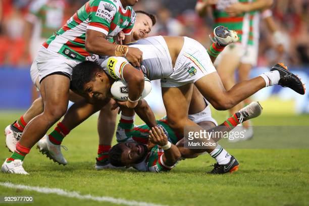 Tyrone Peachey of the Panthers breaking the tackle of Richard Kennar and Alex Johnston of the Rabbitohs on his way to score a try during the round...