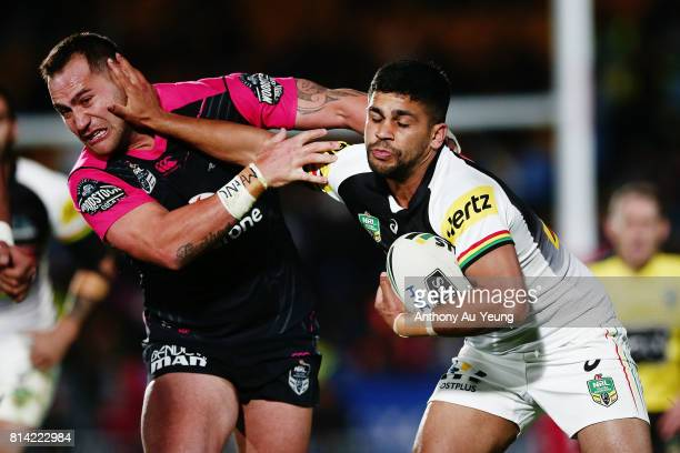 Tyrone Peachey of the Panthers fends against Bodene Thompson of the Warriors during the round 19 NRL match between the New Zealand Warriors and the...