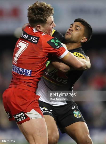Tyrone Peachey of the Panthers is tackled by Kurt Mann of the Dragons during the round 25 NRL match between the Penrith Panthers and the St George...