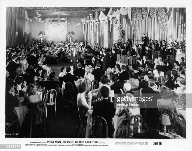 Tyrone Power as pianist Eddy Duchin stands by piano dressed in a tuxedo as audience applauds him in a scene from the film 'The Eddy Duchin Story' 1956