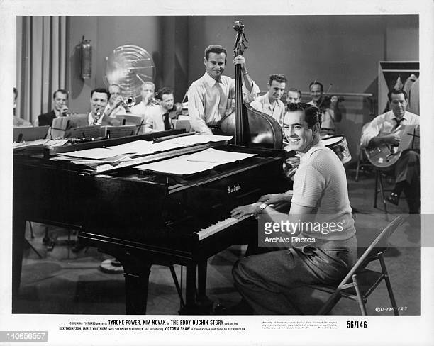 Tyrone Power plays piano along with band members in a scene from the film 'The Eddy Duchin Story' 1956