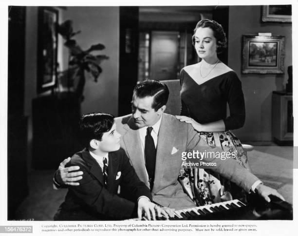 Tyrone Power plays piano with a boy as Victoria Shaw watches in a scene from the film 'The Eddy Duchin Story' 1956