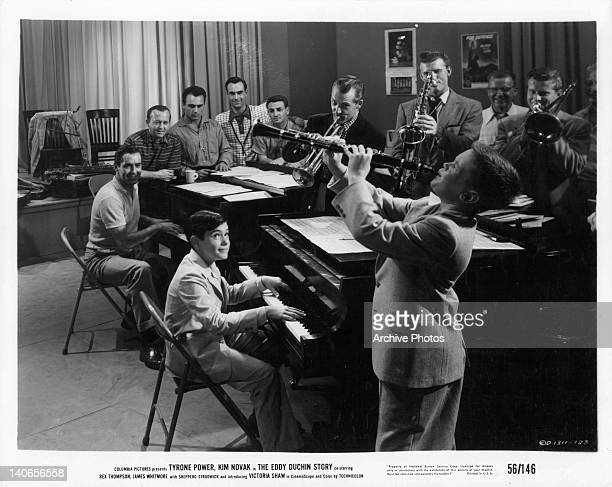 Tyrone Power plays piano with band of men and boys who play various instruments in a scene from the film 'The Eddy Duchin Story' 1956
