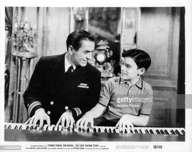 Tyrone Power plays piano with young boy in a scene from the film 'The Eddy Duchin Story' 1956