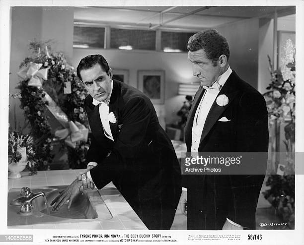 Tyrone Power runs cold water on hand as James Whitmore stands behind him in a scene from the film 'The Eddy Duchin Story' 1956