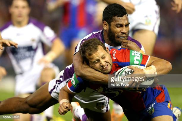 Tyrone Roberts of the Knights scores a try tackled by Sisa Waqa of the Storm during the round 22 NRL match between the Newcastle Knights and the...