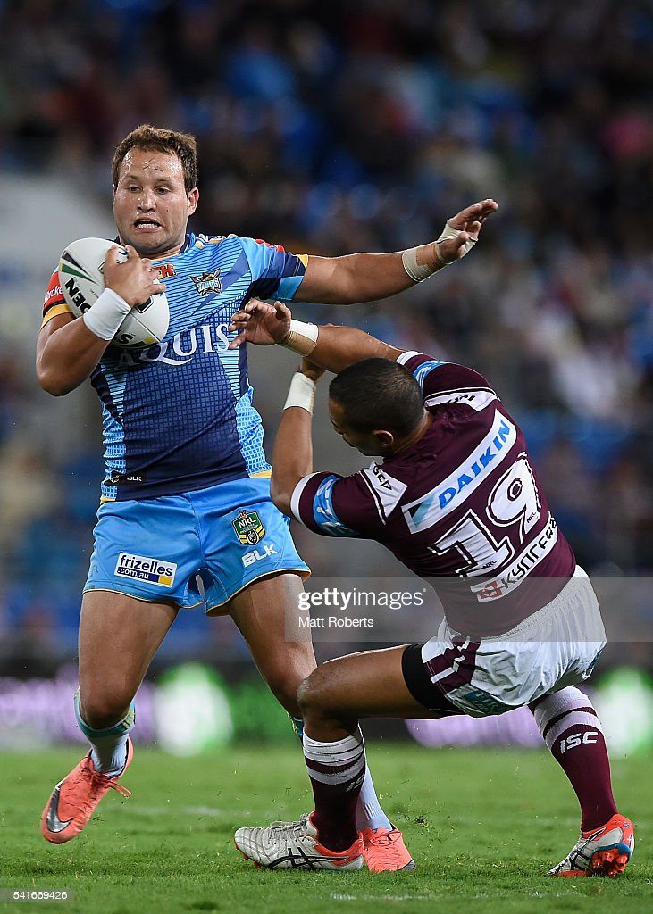 Tyrone Roberts of the Titans break free of the tackle of Pita Godinet of the Sea Eagles during the round 15 NRL match between the Gold Coast Titans and the Manly Sea Eagles at Cbus Super Stadium on June 20, 2016 in Gold Coast, Australia.