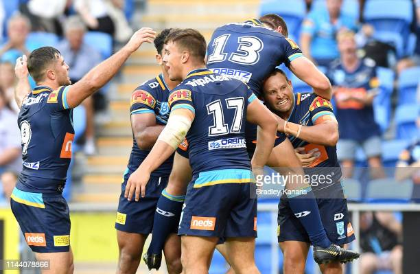 Tyrone Roberts of the Titans is congratulated by team mates after scoring a try during the round 6 NRL match between the Titans and the Knights at...