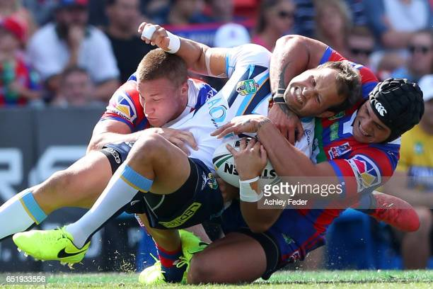 Tyrone Roberts of the Titans is tackled by the Knights defence during the round two NRL match between the Newcastle Knights and the Gold Coast Titans...