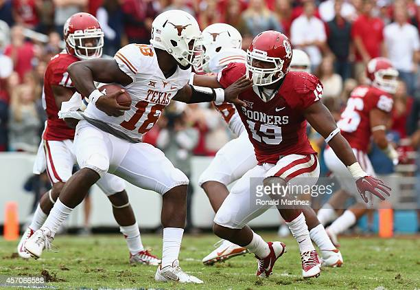 Tyrone Swoopes of the Texas Longhorns runs the ball against Eric Striker of the Oklahoma Sooners at Cotton Bowl on October 11 2014 in Dallas Texas