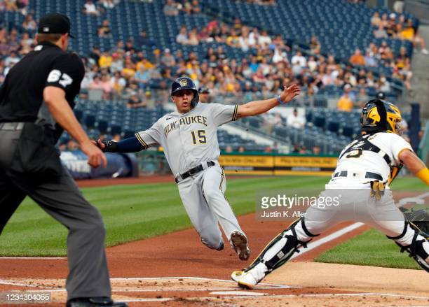 Tyrone Taylor of the Milwaukee Brewers scores on a fielders choice in the second inning against Michael Perez of the Pittsburgh Pirates during the...