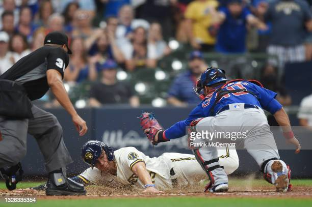 Tyrone Taylor of the Milwaukee Brewers slides safely into home plate ahead of the tag by Willson Contreras of the Chicago Cubs in the fourth inning...