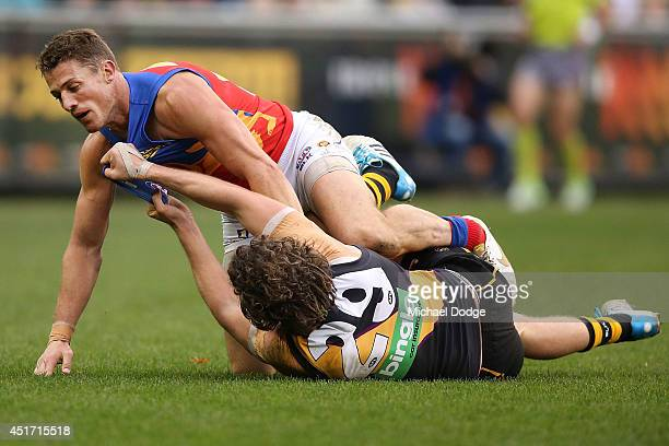 Tyrone Vickery of the Tigers is pinned down by Matt Maguire of the Lions in a wrestle behind play during the round 16 AFL match between the Richmond...