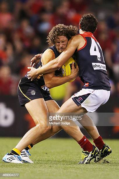 Tyrone Vickery of the Tigers is tackled by Alexis Georgiou of the Demons during the round one AFL NAB Challenge Cup match between the Richmond Tigers...