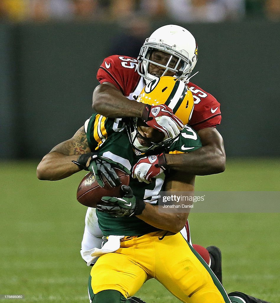 Tyrone Walker #83 of the Green Bay Packers catches a pass and is hit by Javier Arenas #35 of the Arizona Cardinals at Lambeau Field on August 9, 2013 in Green Bay, Wisconsin.