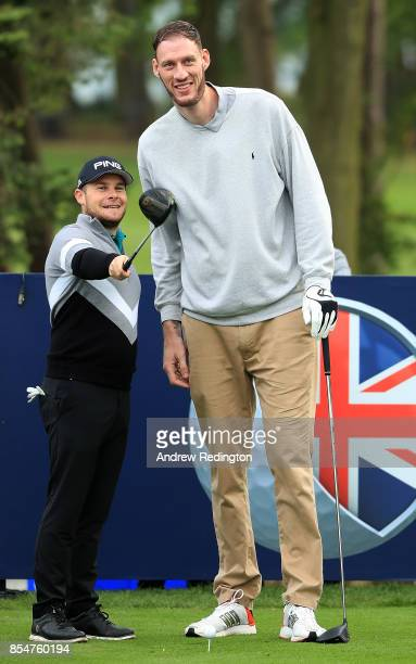 Tyrrell Hatton of England and basketball player Paul Sturgess line up a shot during the pro am ahead of the British Masters at Close House Golf Club...