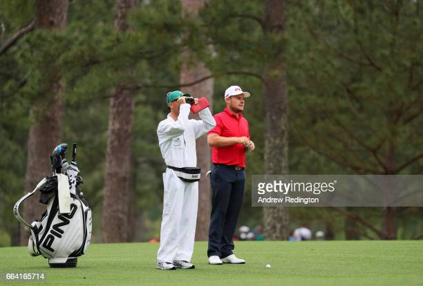 Tyrrell Hatton of England and his caddie Chris Rice on the 14th hole during a practice round prior to the start of the 2017 Masters Tournament at...